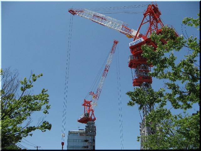 青空にそびえ立つ2機のタワークレーン